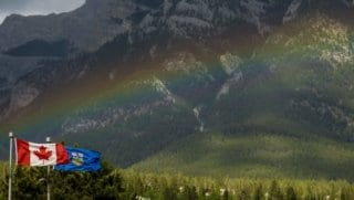 The Canadian flag with a rainbow and mountains