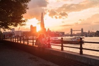 Safest places to live in London: Couple by the river at dusk with Tower Bridge in the background